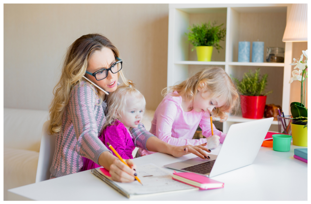 Caucasian woman with two young children. She is at her laptop and on the phone